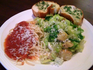 A meatless Italian dinner with bread, salad and pasta.