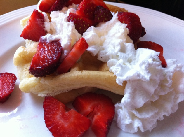 Belgian waffles with sweetened whipped cream and sliced strawberries