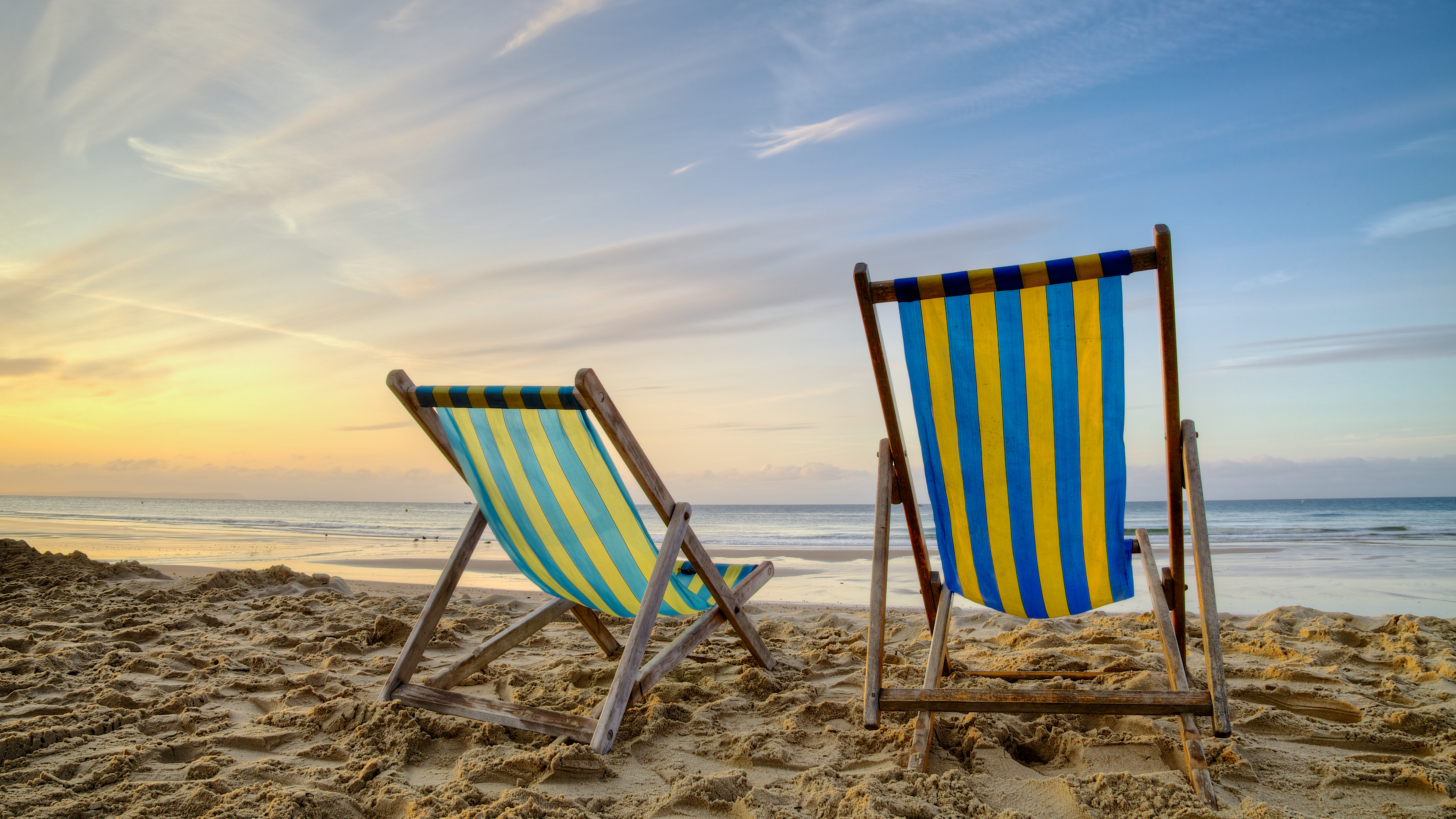 Two empty deck chairs on the beach