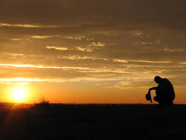 Cowboy praying at dawn