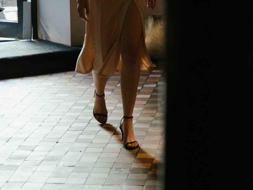 Woman walking across white tiles