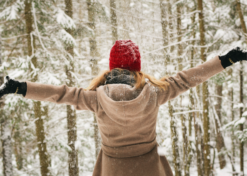 Woman staring at snowy forest with arms spread wide
