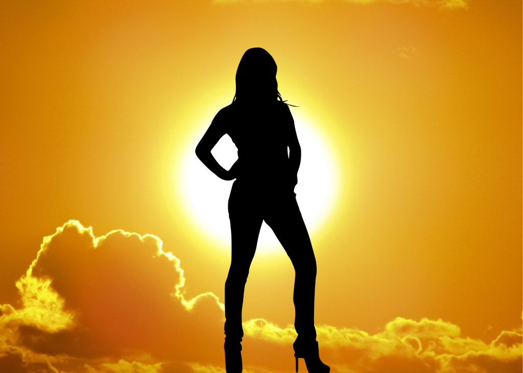Silhouette of woman standing in daylight.